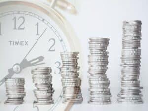 pilhas de moeda com relógio ao fundo representando ações de baixo resultado