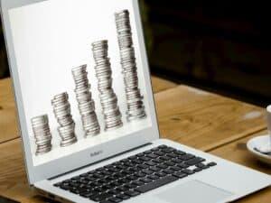 notebook mostrando pilha de moedas em sua tela representando investimentos com foco em dividendos
