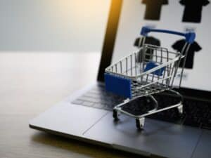 imagem ilustrativa de carrinho de compras em miniatura em cima de um notebook, representando lojas online para evitar na black friday