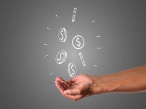 mão com ilustração de moedas, representando lote de restituição do imposto de renda