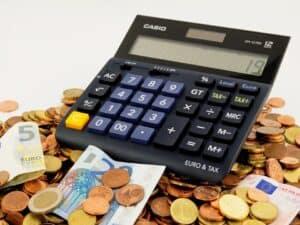 calculadora e moedas, representando manobras fiscais para elevar gastos podem fazer juros subirem mesmo com a manutenção do teto de gastos