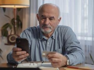 Imagem de um senhor de idade segurando um cartão de crédito em uma das mãos e um celular em outra. Foto representa o post sobre pagar boleto com cartão de crédito
