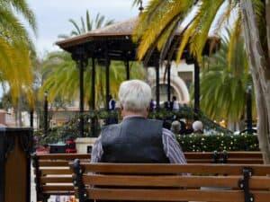 idoso, de costas, sentado em banco de praça representando pedido de revisão de aposentadoria do INSS