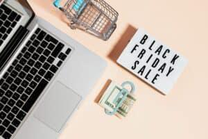 computador e placa falando de cupons de desconto na black friday