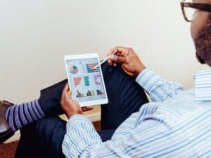 homem analisando gráficos no tablet, representando plataforma de educação financeira