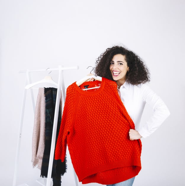 mulher mostra roupas que deseja revender para ganhar dinheiro online ou offline