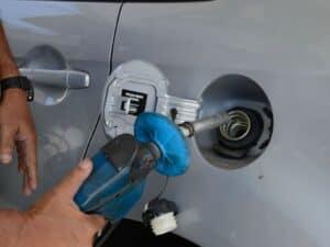 Bomba no tanque de combustível de um carro, simbolizando o preço da gasolina.
