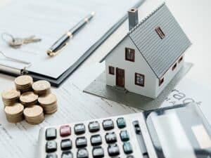 maquete de casa, calculadora e moedas, representando preço do aluguel cai