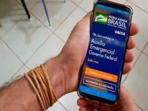 mão segurando smartphone aberto no aplicativo do Auxílio Emergencial representando processos contra indeferimento do auxílio emergencial