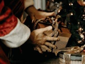 papai noel colocando presente em árvore de natal, representando programa de cartas ao papai noel