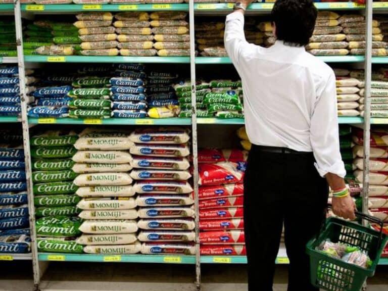 Homem em prateleira de supermercado pegando um arroz, produto que contribuiu para a alta da projeção da inflação
