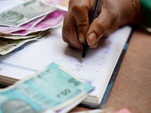 mão escrevendo em caderno com notas de dinheiro no entorno representando reparcelamento do Simples Nacional