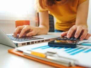 Imagem de uma mulher usando um computador e uma calculadora para entender qual é o score mínimo para cartão de crédito
