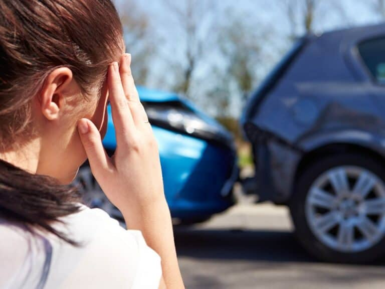 mulher observando batida de carro, representando seguros dos automóveis mais vendidos em outubro