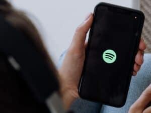 Pessoa segurando o celular com o aplicativo do Spotify aberto, representando recurso para impulsionamento de músicas
