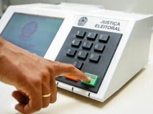 dedo apertando confirma em urna eletrônica, representando trabalhar nas eleições