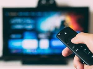 controle remoto apontado para televisão representando tv na black friday