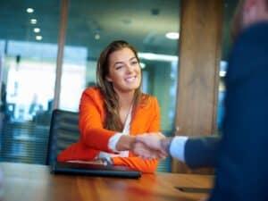 mulher apertando a mão de contratante, representando vagas de estágio e trainee