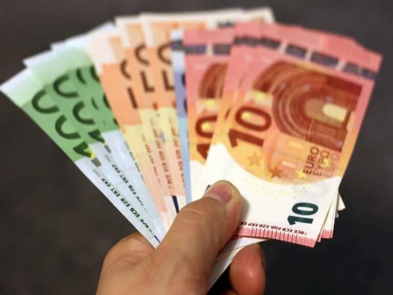 """mão entregando cédulas de dinheiro representando BC quer """"lentamente"""" substituir o uso de dinheiro físico"""