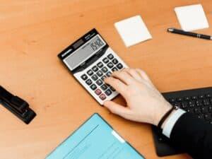 Imagem de uma pessoa sentada fazendo cálculos, eles são importantes para aprender Como consultar score para financiamento