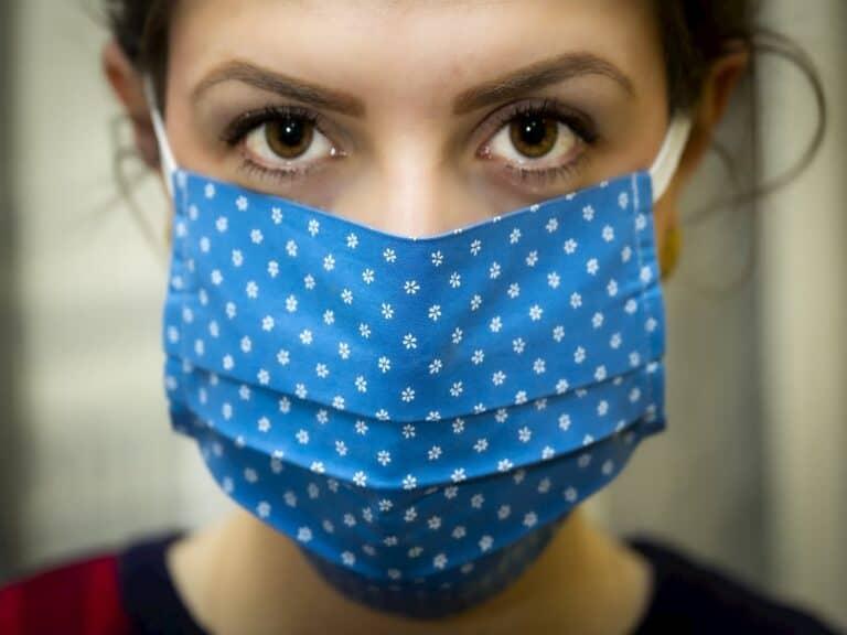 close no rosto de mulher com máscara representando Covid-19 pega no trabalho