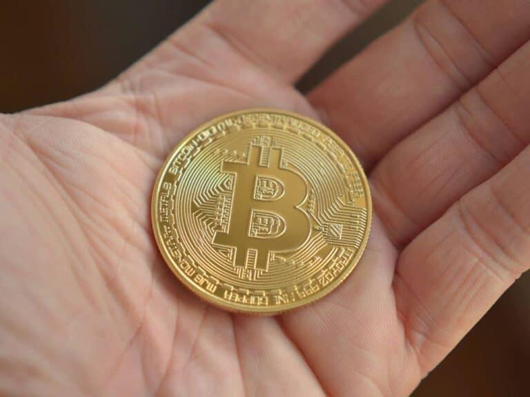 mão segurando moeda de bitcoin, representando criptoativos em capital social de empresas