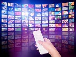 mão apontando controle remoto para tv, representando Discovery+