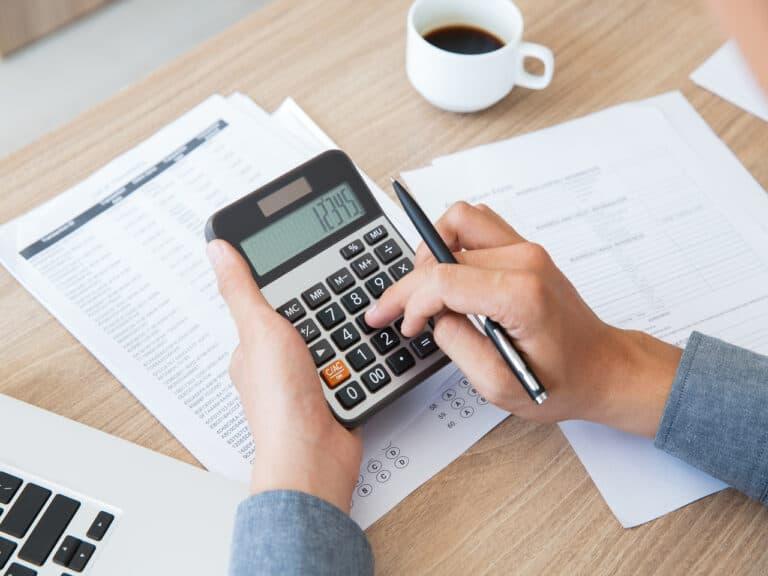 homem com calculadora e caneta na mão fazendo cálculos com folhas na mesa e uma xícara de café preto ao lado, representando ir 2021