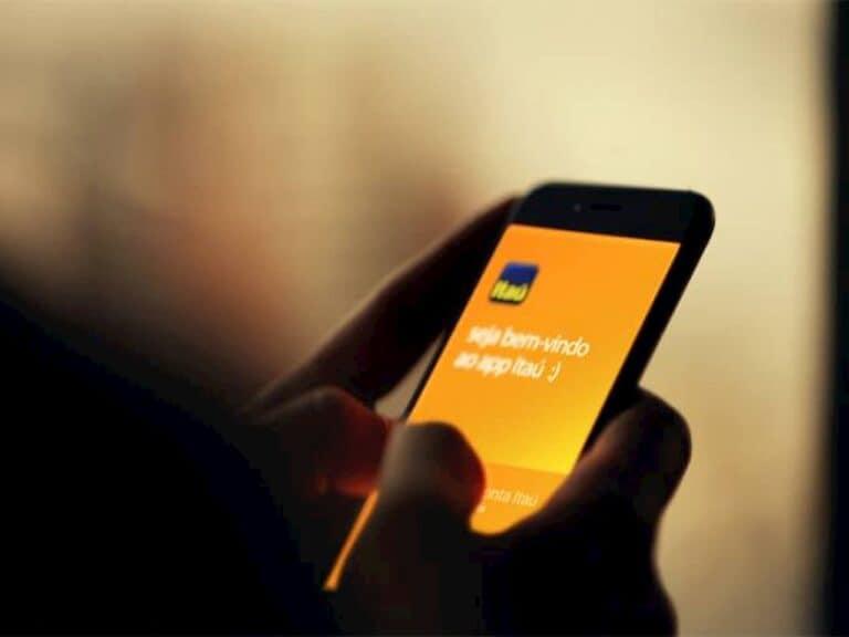 mão segurando smartphone abeto em aplicativo do Itaú Unibanco representando Itaú Unibanco contrata
