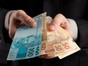 mãos segurando cédulas de real, representando cobrança indevida de crédito consignado