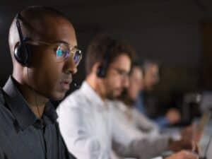 Homens trabalham no call center representando o SAC Santander