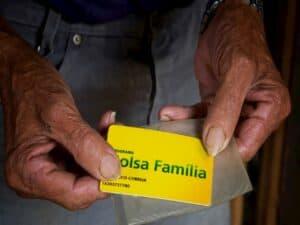 mãos segurando cartão do Bolsa Família representando Senado tem projeto para reformular programas sociais