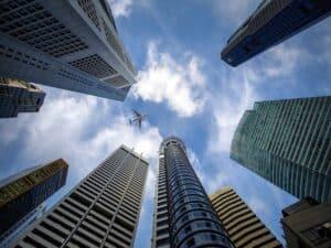 avião sobrevoando arranha-céus representando aplicações fora do país