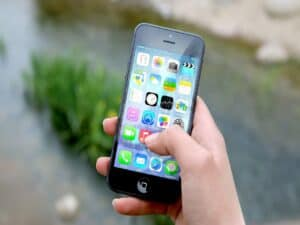 mão segurando smartphone representando popularidade pós-pandemia do investidor comum nos apps online