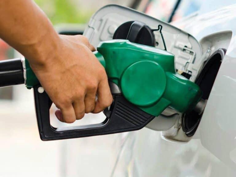 mão com uma bomba de combustível abastecendo um carro, representando aumento dos combustíveis