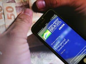Notas de reais e a interface do aplicativo do Auxílio Emergencial em um celular.