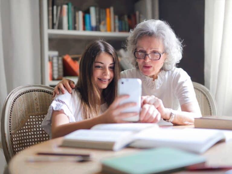 menina ensinando idosa a mexer no celular representando cadastro no inss