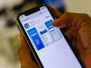 celular com aplicativo caixa tem, representando bolsa família em conta digital