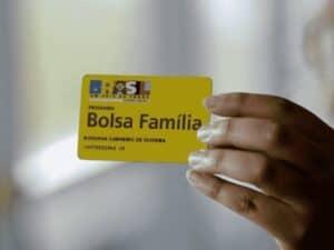 mão segurando cartão do bolsa família, representando calendário bolsa família dezembro