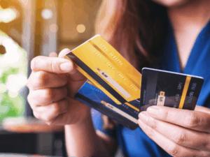 Imagem de uma mulher com três cartões de crédito na mão, representando nosso conteúdo sobre cartão de crédito aprovado na hora