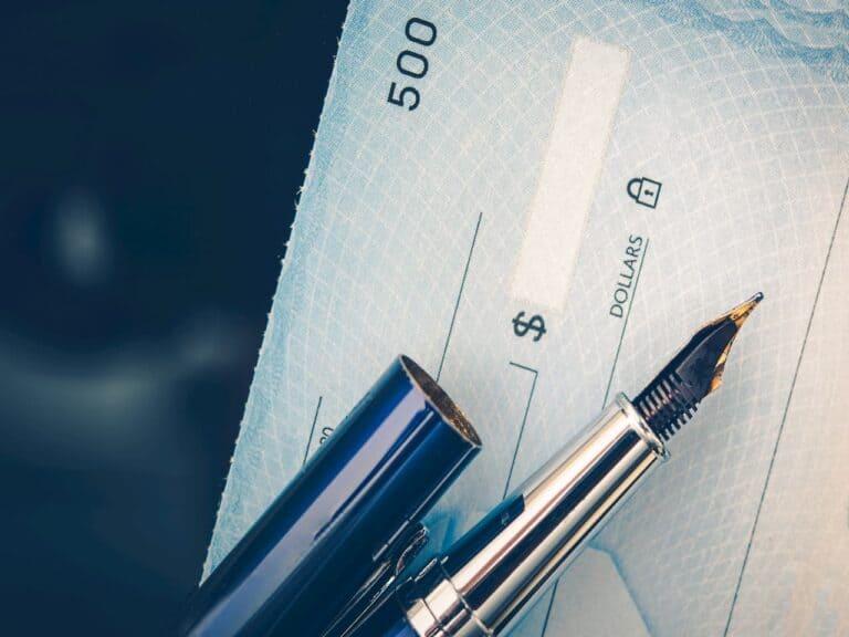 caneta sem tampa e cheque representando cheque especial encolhe