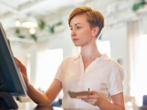 mulher de cabelos curtos e camisa de manga curta está com um cartão ou papel em uma das mãos e na outra mexendo em um computador