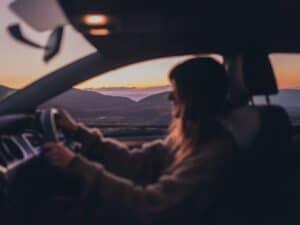 Imagem de uma mulher dirigindo um veículo, ilustrando o conteúdo que debate a respeito da dúvida de comprar ou alugar um carro
