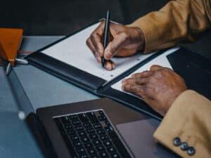 pessoa escrevendo em caderno, representando declaracao de investimentos irpf