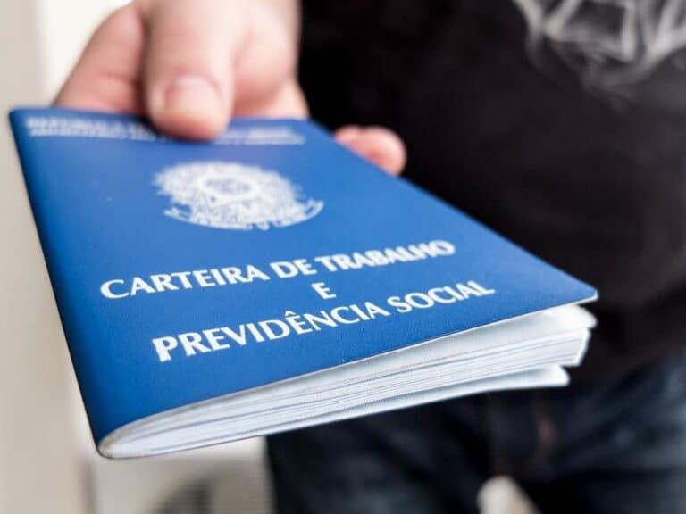 mão segurando carteira de trabalho, representando Demissões na Pandemia
