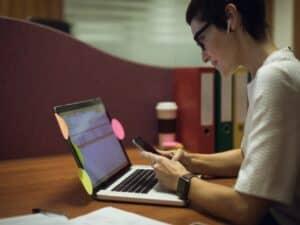 Empreendedora trabalha no celular e notebook fazendo dropshipping