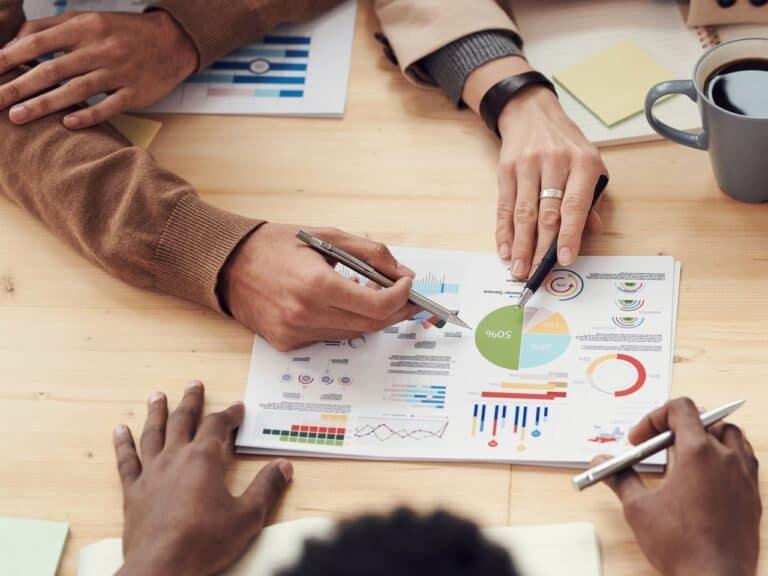 pessoas manipulando gráficos, representando educacao financeira em empresas