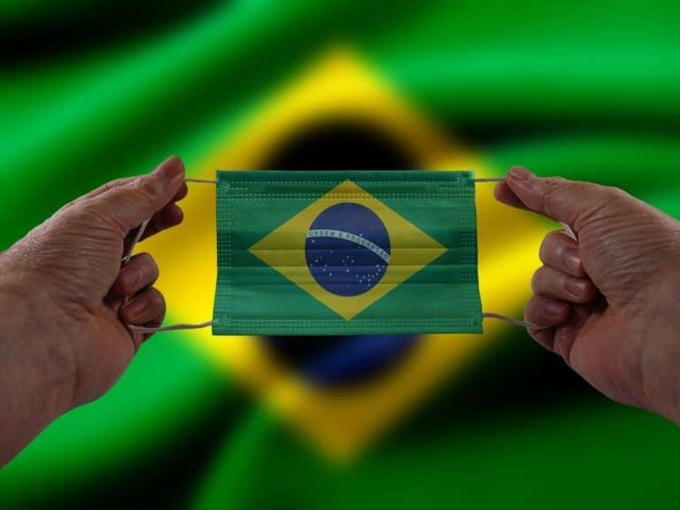 fundo com a bandeira do Brasil e suas mãos segurando uma máscara com a bandeira do Brasil desenhada, representando estado de calamidade pública