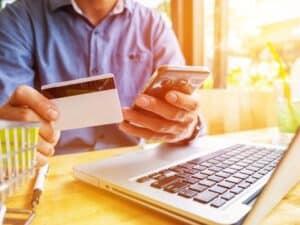 homem sentado com o celular em uma mão e um cartão de crédito na outra e um computador em frente dele