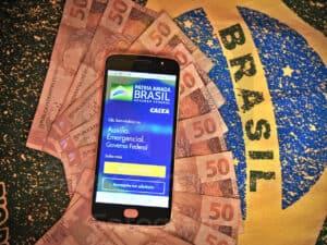 celular com a tela do auxílio emergencial aberta em cima de várias notas de 50 reais e a bandeira do Brasil desenhada embaixo